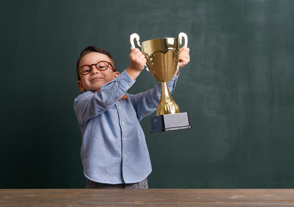 young boy in business clothing holding a trophy