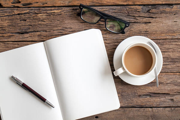 blank notebook on a wooden table next to a pair of glasses and a coffee cup
