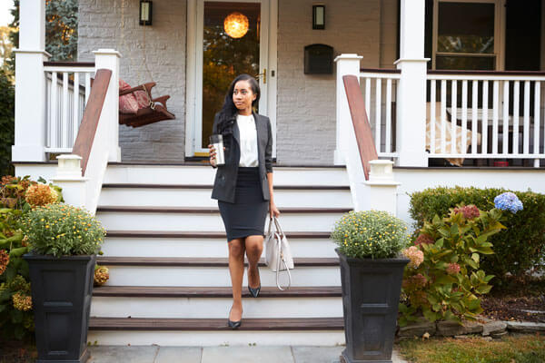 business women walking down her front porch stairs with her purse and coffee