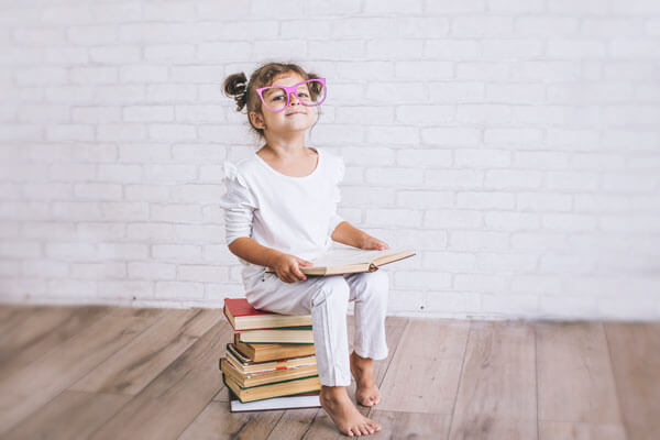 young girl with funny looking, large glasses sits on a pile of books while holding a book in her hand