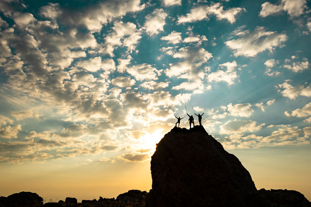 people triumphantly standing on top of a mountain