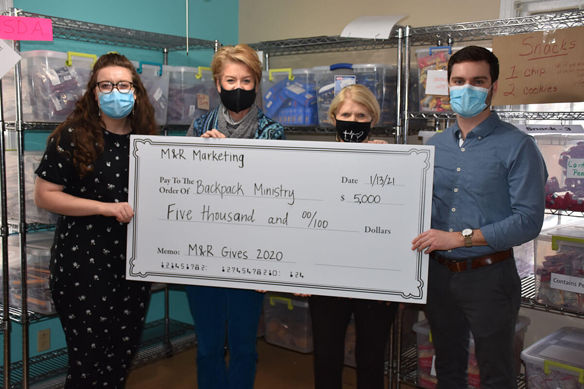 M&R presents a check to Backpack Ministry